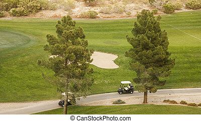 Golf Carts on Path - Two golf carts on a path by green and...