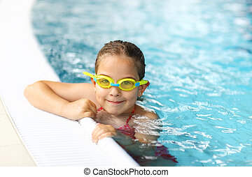 Schoolgirl with goggles in swimming pool - Cute girl with...