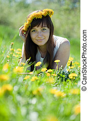 girl lying  in dandelion wreath