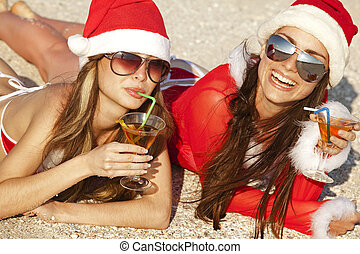 Women in christmas suit with martini on the beach - Two...