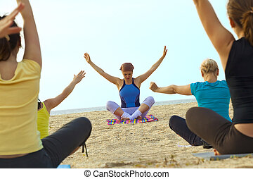 Women doing fitness exercise on a beach - Young women doing...
