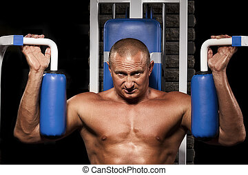 Muscular man doing weightlifting in gym