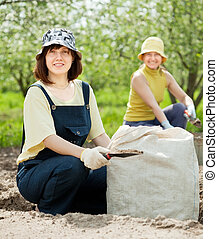women fertilizes soil - Two women fertilizes the soil in...