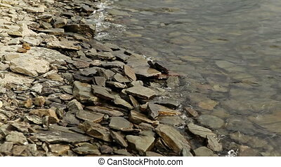 Waves on Rocky Shore - waves on rocky shore at cloudy summer...