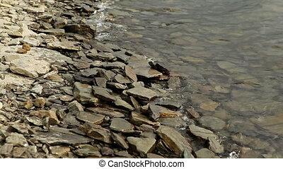Waves on Rocky Shore - waves on rocky shore at cloudy summer...