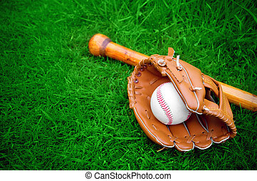 baseball bat, ball and glove on grass with copy space
