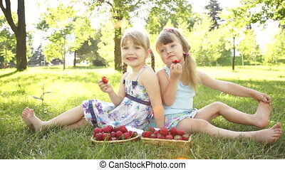 Funny girls eating strawberries.