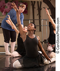 Kneeling Dance Students - Ballet class teacher helps...
