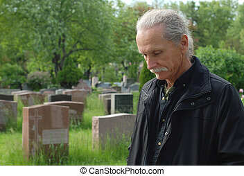 Man in cemetery - Sorrowful man standing in cemetery with...