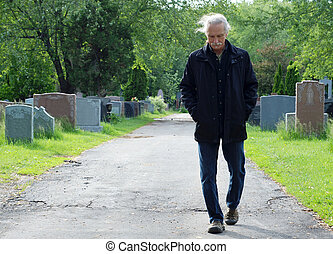 Man walking in cemetery - Middle aged man walking in...