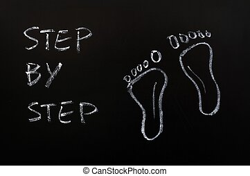 Footprints and the words step by step drawn with chalk -...