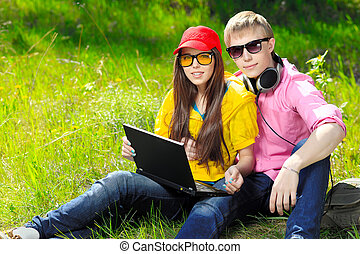 modern teenagers - Couple of modern teenagers sitting with a...
