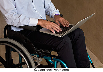 Man on Wheelchair Using Laptop - Close-up of man on...