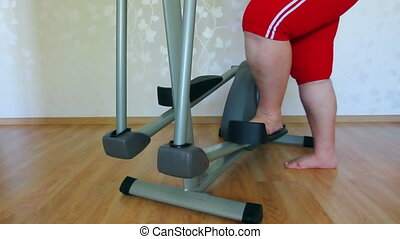 overweight woman legs exercising on trainer ellipsoid