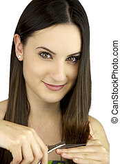 Young woman smiling cutting her split ends smiling