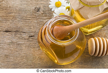 glass jar of honey and stick on wood background