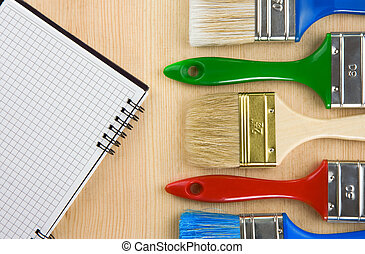 colorful paintbrush on wood background