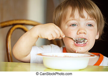 Child himself eats cereal - two-year child himself eats...
