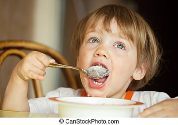 Child himself eats cereal with a spoon
