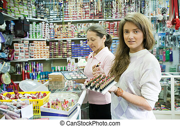Two women chooses   cosmetic at cosmetics  shop