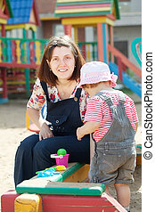 mother with toddler in sandbox - happy mother with toddler...