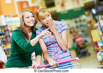 Two shopping woman with cart at supermarket - Two suprised...