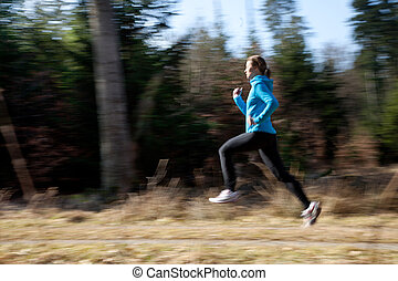 A young woman wearing sports gear running through the woods...