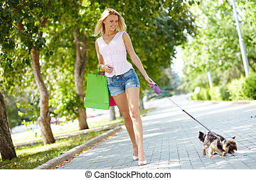 Leisure - Portrait of happy female strolling with her pet at...