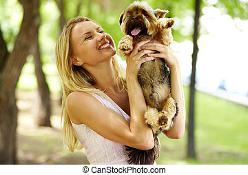 Playing with dog - Portrait of happy female holding pet and...