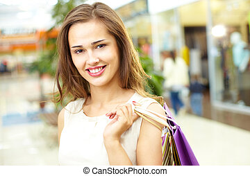 Happy shopper - Portrait of a cheerful girl holding a bunch...