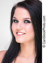 Closeup of a cheerful young woman smiling on white...