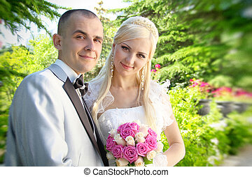 smiling bride and groom - bride holding a bouquet of flowers...
