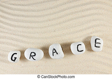 Grace word on group of stones with sand background