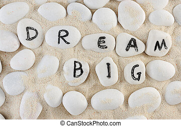 Dream big words among group of stones on the sand