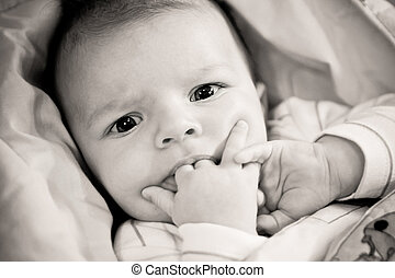 adorable baby with fingers in his mouth