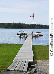 Canadian Boat Dock - A Canadian flag flutters over a long...