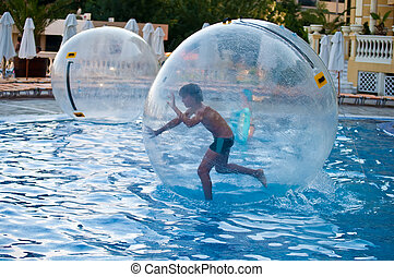 Games on the water - Boy in the air ball in the water in the...