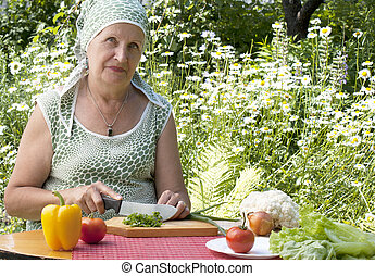 The happy woman cuts salad from fresh appetizing vegetables...