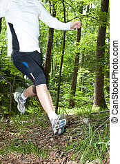 Trail run - Trailrunner running at a fast pace through the...