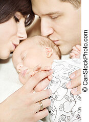 Parents with newborn baby lying down and kissing child....