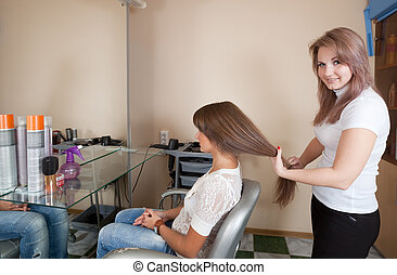 hair stylist working with long-haired girl
