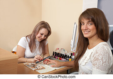 manicurist working with female nails in salon. Focus on...