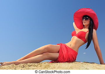 red hat - Beautiful young woman in bikini on a sunny beach