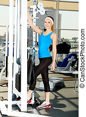 gym centre - Young sporty woman doing exercises in the gym...