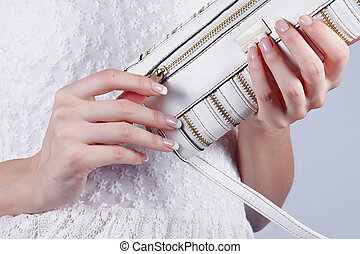 Beautiful female hands with manicure with a handbag