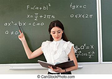 smiling teacher writes on blackboard - The teacher in the...