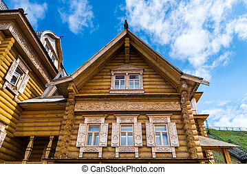 Wooden log house with decorated windows, Russian traditional...
