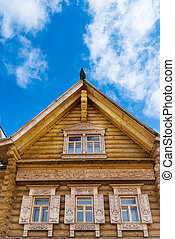 Wooden decorated windows in log house under blue sky,...