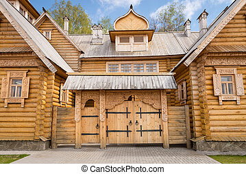 Wooden log house with decorated windows and gate, Russian...