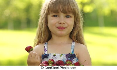 Smiling child eating strawberries
